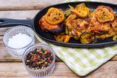 stock photo of thighs  - Delicious baked chicken thighs with lemon slices onion and zucchini served in cast - JPG