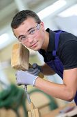 pic of wood pieces  - Young apprentice in carpentry working piece of wood - JPG