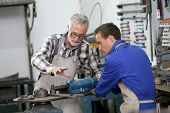 picture of ironworker  - Young man in ironworks training with professional teacher - JPG