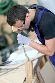 stock photo of wood pieces  - Young apprentice in carpentry working piece of wood - JPG