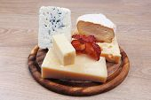 foto of cheese platter  - various types of cheese on wooden platter over wooden table - JPG