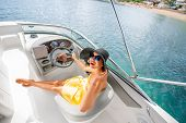 picture of top-hat  - Young and pretty woman in yellow skirt and swimsuit with hat and sunglasses driving luxury yacht in the sea - JPG