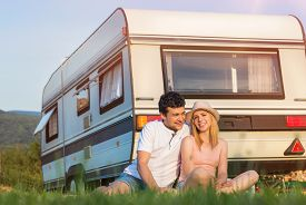 foto of camper  - Beautiful young couple in front of a camper van on a summer day - JPG