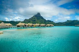 pic of french polynesia  - Luxury overwater thatched roof bungalow resort in a vacation resort in the clear blue lagoon with a view on the tropical island of Bora Bora near Tahiti in French Polynesia - JPG