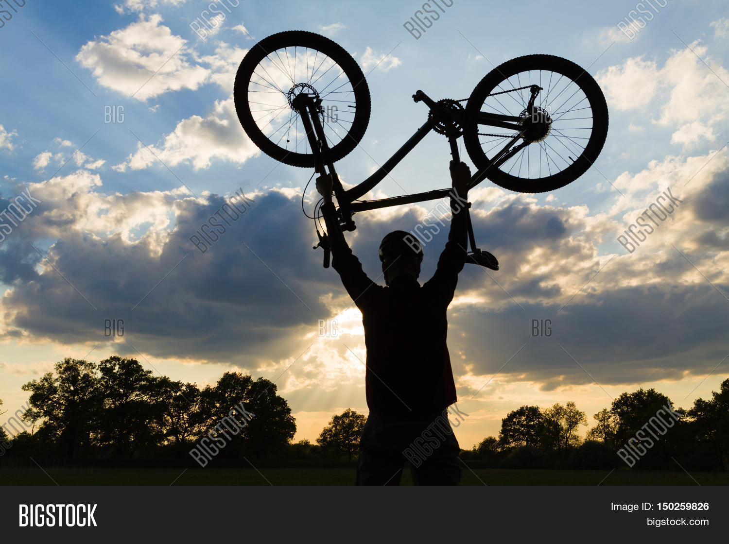 mountain biker silhouette in summer mtb rider holding a bike upside down at sunset