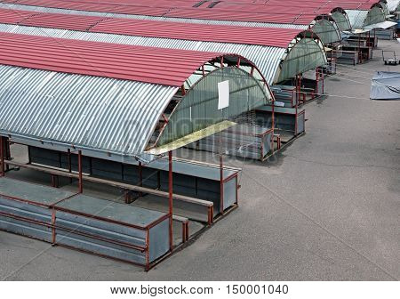 Top view of an empty market. Rows of metal awnings in perspective.