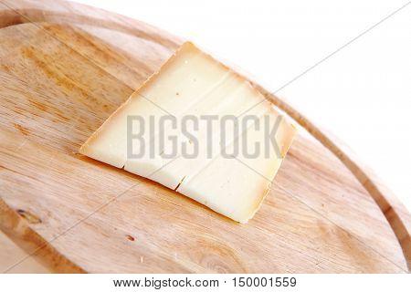 piece light swiss cheese on wooden board