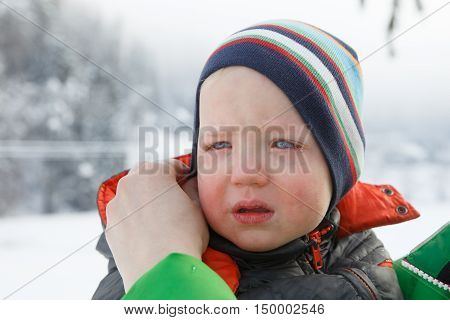Little boy crying his mother trying to console him in a winter landscape. Temper tantrum distress and emotional outburst concept.