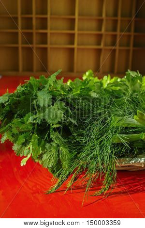 Fresh green herbs in the wicker basket - parsley coriander green onion dill on red background