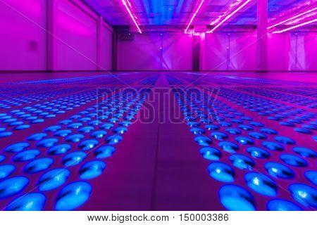 Ventilation holes in the floor of an empty server room.
