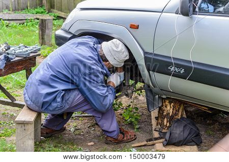 The man repairs car in the field. Repair their own hands.