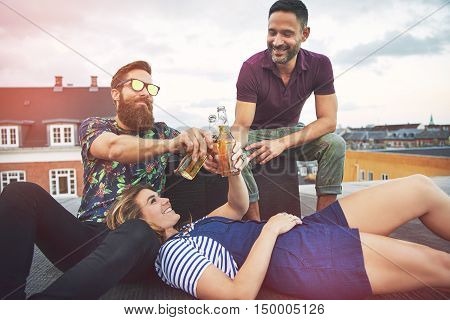 Three adults enjoying beer and toasting with bottles on top of roof in European city during summer