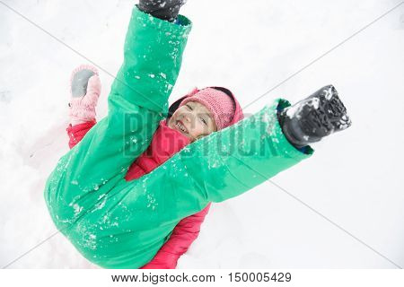 Playful girl with braids playing in snow snow diving having fun and being active. Natural lifestyle and free childhood concept with copy space.