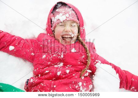 Playful girl with braids playing in snow throwing it in the air having fun enjoying and being active. Natural lifestyle and free childhood concept with copy space.