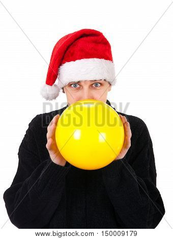 Young Man in Santa Hat inflate a Yellow Balloon Isolated on the White Background