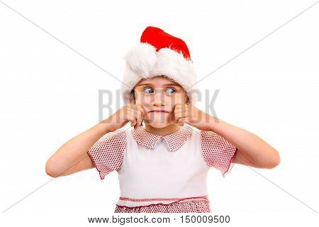 Small Girl in Santa Hat try to make a smile on the White Background