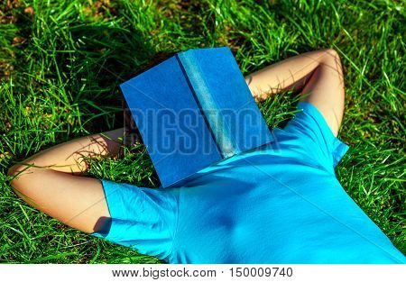 Person take a rest on the Green Grass with a Book