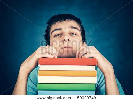 Toned Photo of Sad Student with a Books on the Blue Background