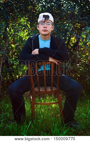 Teenager sit on the Chair on the Nature Background