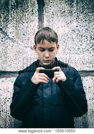 Toned Photo of Kid play with Cellphone by the Wall