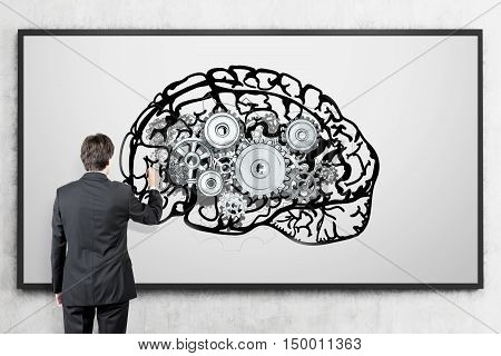 Rear view of man in suit standing against concrete wall with brain sketch and gears on whiteboard. Concept of brain and behaviour studying