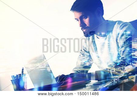 Side view of bearded caucasian businessman working on laptop at office desk with pencil glass and office tools. Toned image. Double exposure