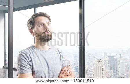Portrait of bearded man in T-shirt standing near panoramic window with cityscape and planning to conquer the world. Mock up