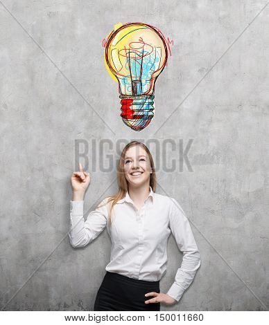 Portrait of smiling blond businesswoman pointing at large light bulb sketch on concrete wall above her head. Concept of new idea