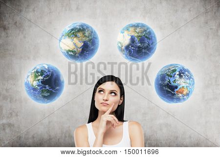Girl with black hair standing against concrete wall background and looking at four globes showing different parts of the world. Concept of globalization and international company. Toned image