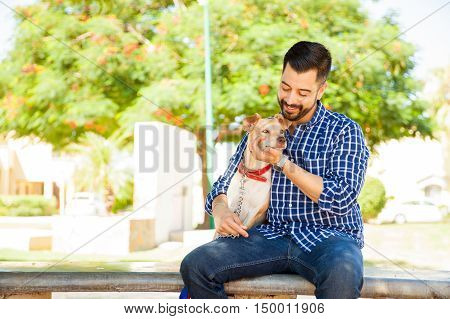Young Man Petting His Dog At The Park