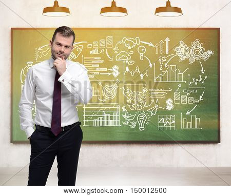 Doubtful businessman looking at the viewer standing in room with startup icons on green chalkboard. Concept of tough choices. Toned image