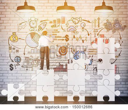 Rear view of businessman standing on puzzle pieces and drawing business sketch on brick wall. Concept of management. Toned image