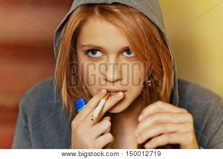 Teenage woman drinking beer and smoking cigarette