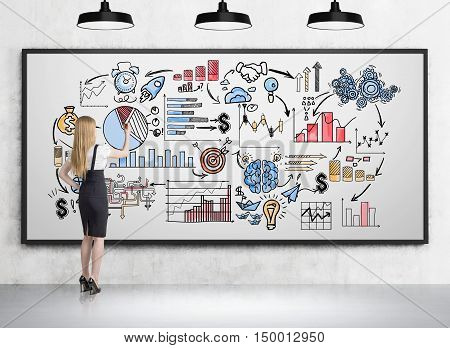 Side view of blond girl drawing sketches on whiteboard in room with concrete walls and floor. Concept of business