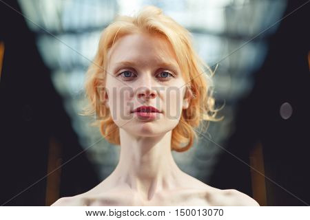 Photo ginger girl close up on background of glass ceiling, tinted photo