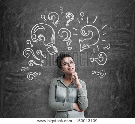 African American girl being attacked by question marks drawn on blackboard. Concept of searching for an answer.