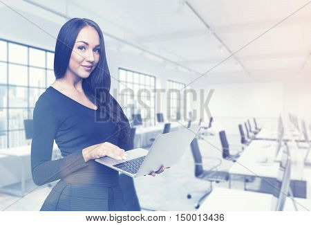 Close up of beautiful girl in black dress is standing with her laptop in office and looking at the viewer. Concept of good secretary. 3d rendering. Mock up. Toned image