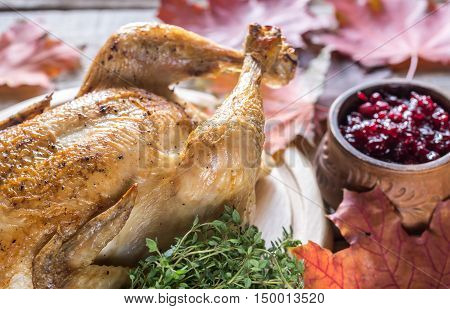 Roasted chicken with cranberry sauce on the wooden background