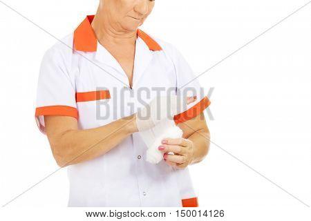 Elderly female doctor or nurse use bandage on her hand