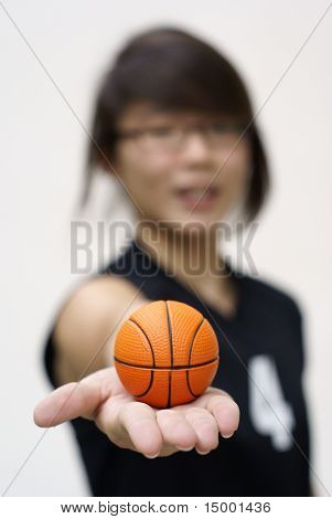 Asian teen holding tiny basketball in hand