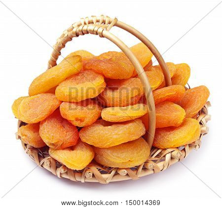 Dried apricots in a wicker basket on white