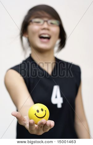 Asian lady holding yellow happy ball