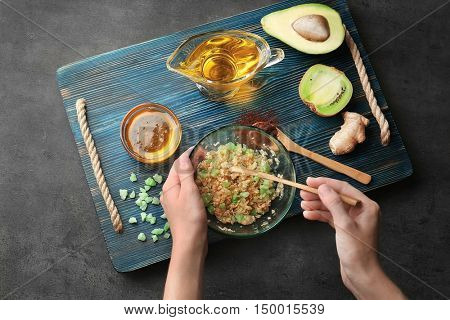 Female hands making nourishing facial mask with natural ingredients on wooden board