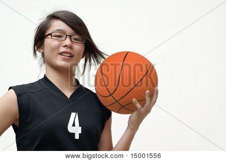 Smiling asian female holding basketball