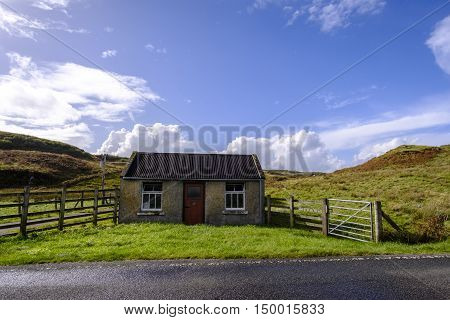 Old farm outbuilding in remote Isle of Skye Scotland countryside with wooden fence and metal gate
