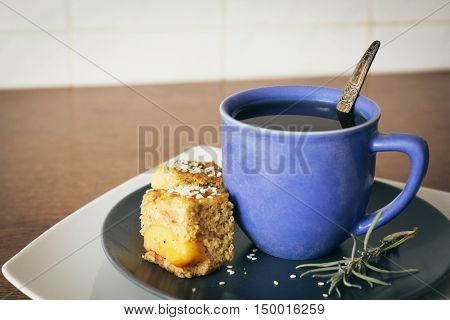 Blue cup of tea and homemade quince apple pie on wooden table