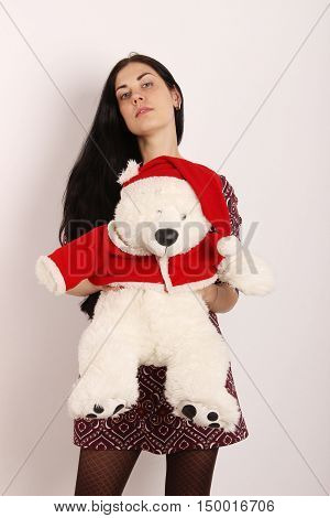 Christmas, X-mas, New Year, holidays,people concept - the portrait of standing young adult brunette woman hugging a big white christmas teddy bear on light background