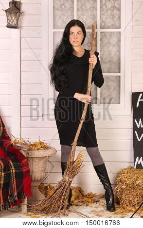 Halloween, autumn concept. Sexy brunette witch woman in black dress with broomstick in hands standing on autumn veranda