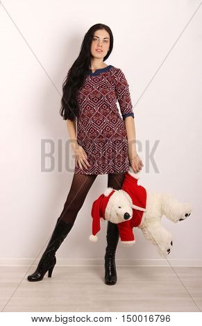 people, holiday, Christmas, New Year concept - the portrait of young adult slender brunette woman with big white christmas teddy bear toy over white background
