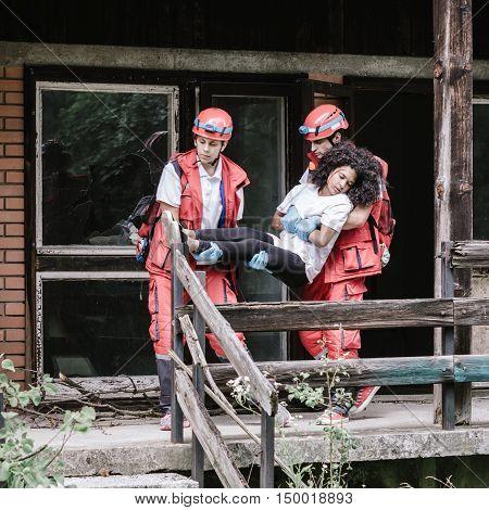 Rescue team evacuating disaster victim, toned image